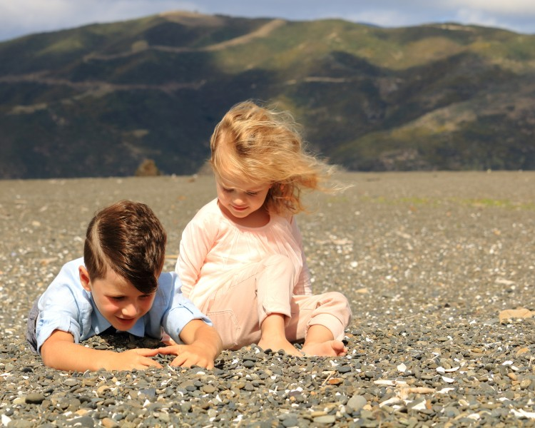 Family portrait - Two children playing on a beach by Sam Davis Professional family portrait Photographer