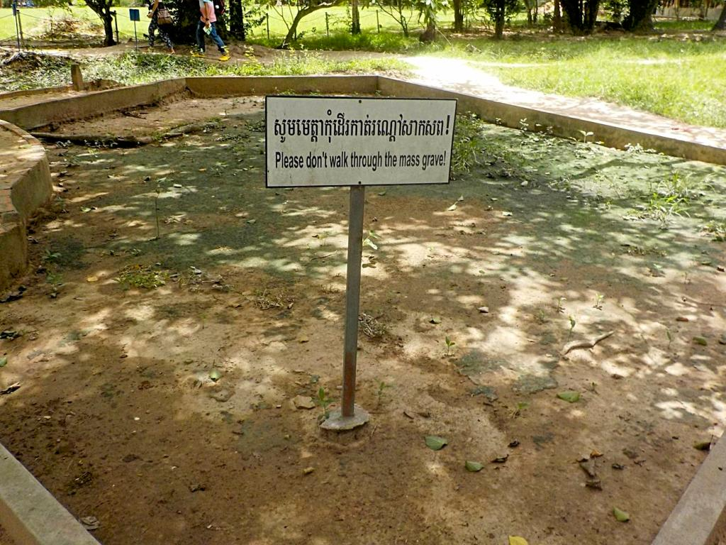 """A sign reading """"Please don't walk through the mass grave"""" at the Killing Fields, Cambodia by Sam Davis Photographer Professional Travel"""
