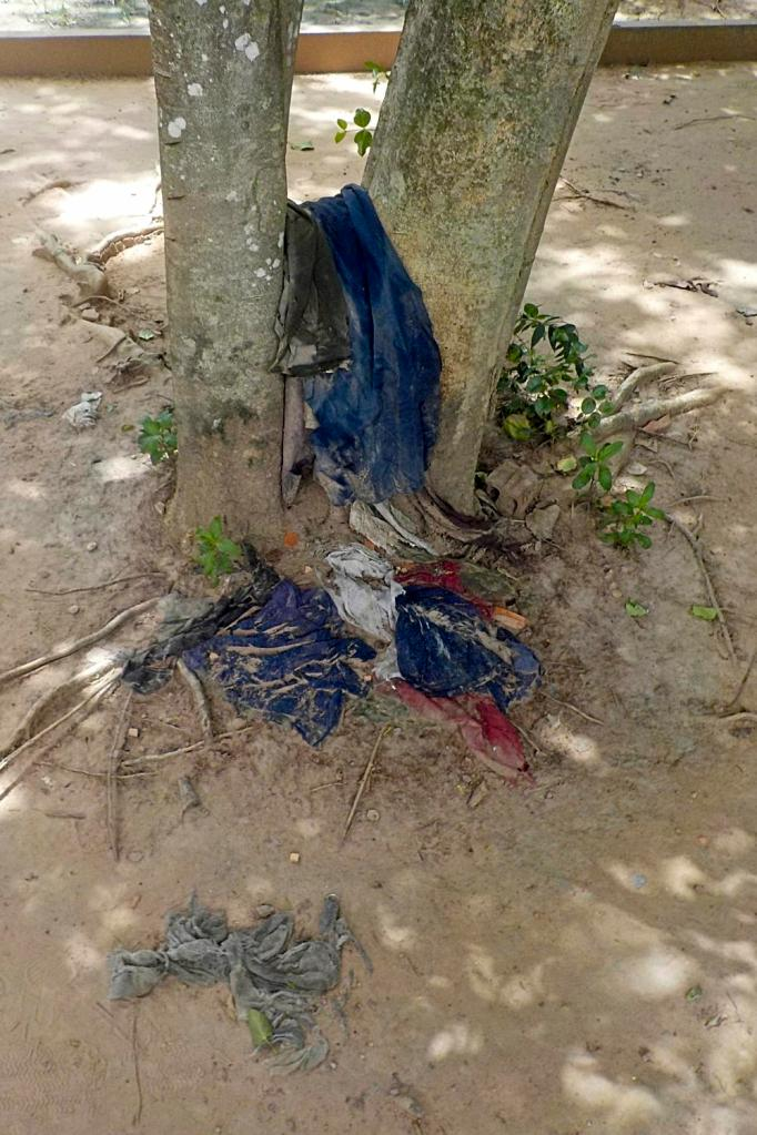 Clothes of victims slung on a tree at the Killing Fields, Cambodia by Sam Davis Photographer Professional Travel