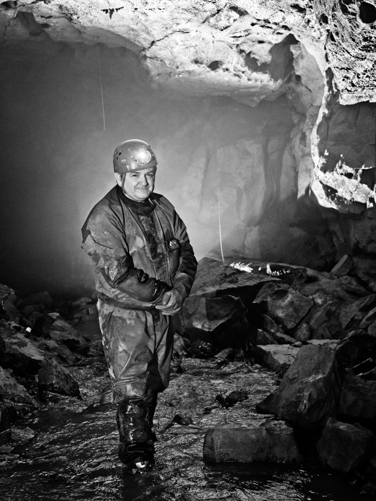 Caver in Poacher's Cave, Flintshire, Wales by Sam Davis Photographer speleology underground black and white caving potholing cave rescue