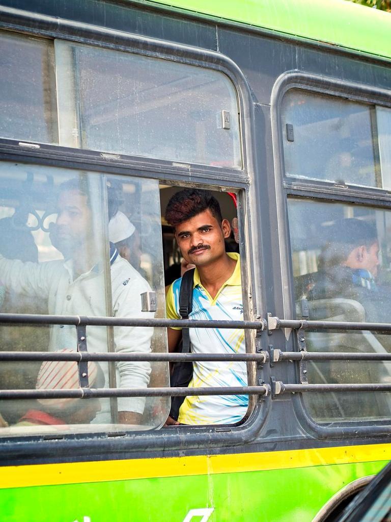 Student on a green bus, Delhi, India by Sam Davis Professional Travel Portrait Photographer