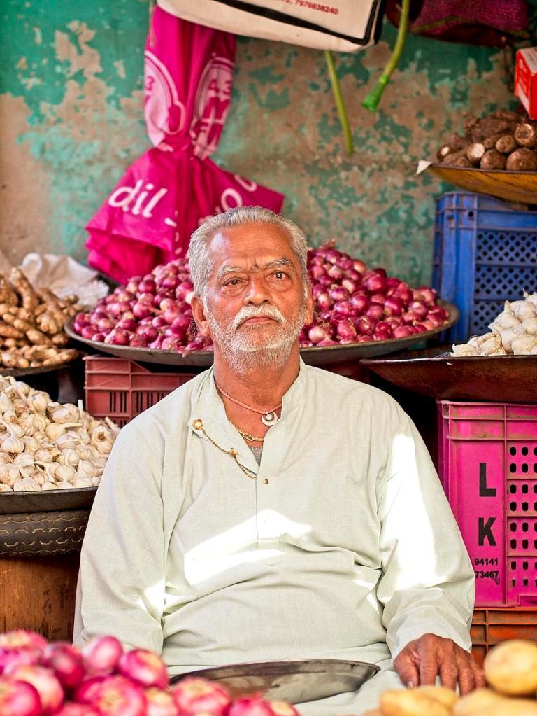 Indian man at a fruit stall, Jodhpur market, Rajasthan, India by Sam Davis Professional Travel Portrait Photographer