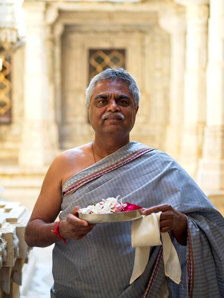 A priest makes an offering at the Jain Temple, Udaipur, Rajasthan, India by Sam Davis Professional Travel Portrait Photographer