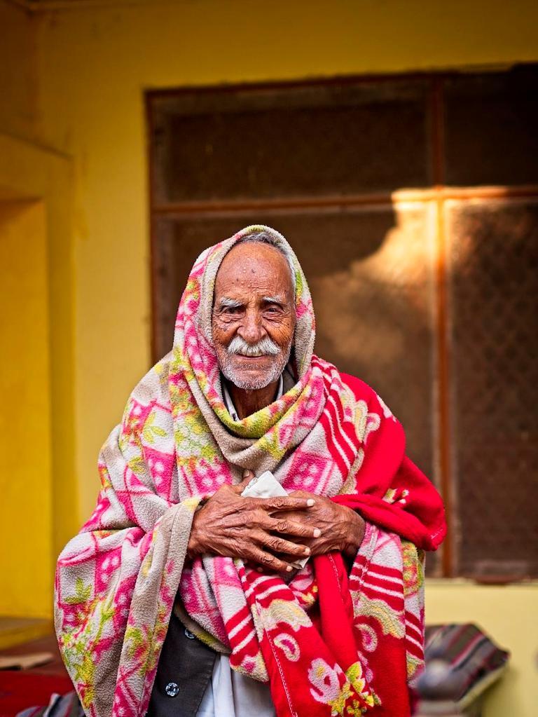 An Indian Man greets us in his village, Jojawar, India by Sam Davis Professional Travel Portrait Photographer