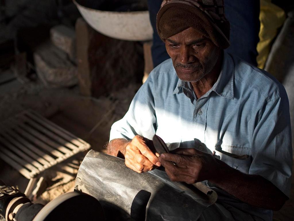 A smith checks the quality of his scissors, Jojawar, India by Sam Davis Professional Travel Portrait Photographer