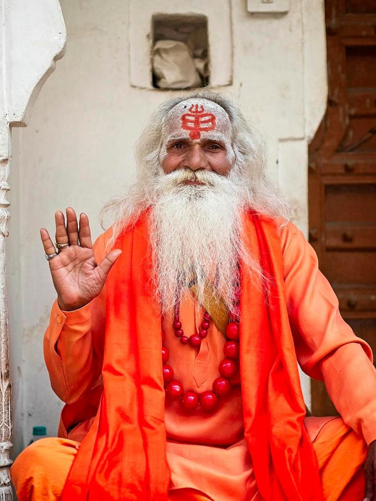 A priest greets us in Pushkar, India by Sam Davis Photographer Travel Portrait hindu orange