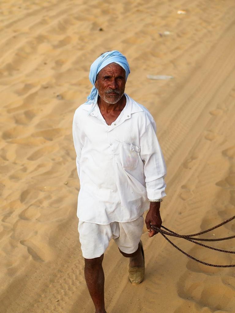 An Indian man walks in the desert in Pushkar, Rajasthan, India, by Sam Davis Professional Travel Portrait Tourism Photographer