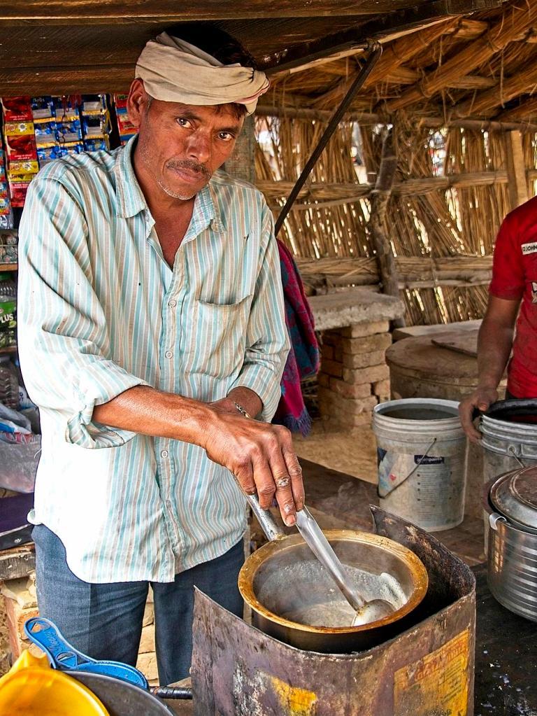 Indian Man making Chai Masala tea at a rest area martet, Rajasthan, India by Sam Davis Professional Travel Portrait Street Photographer