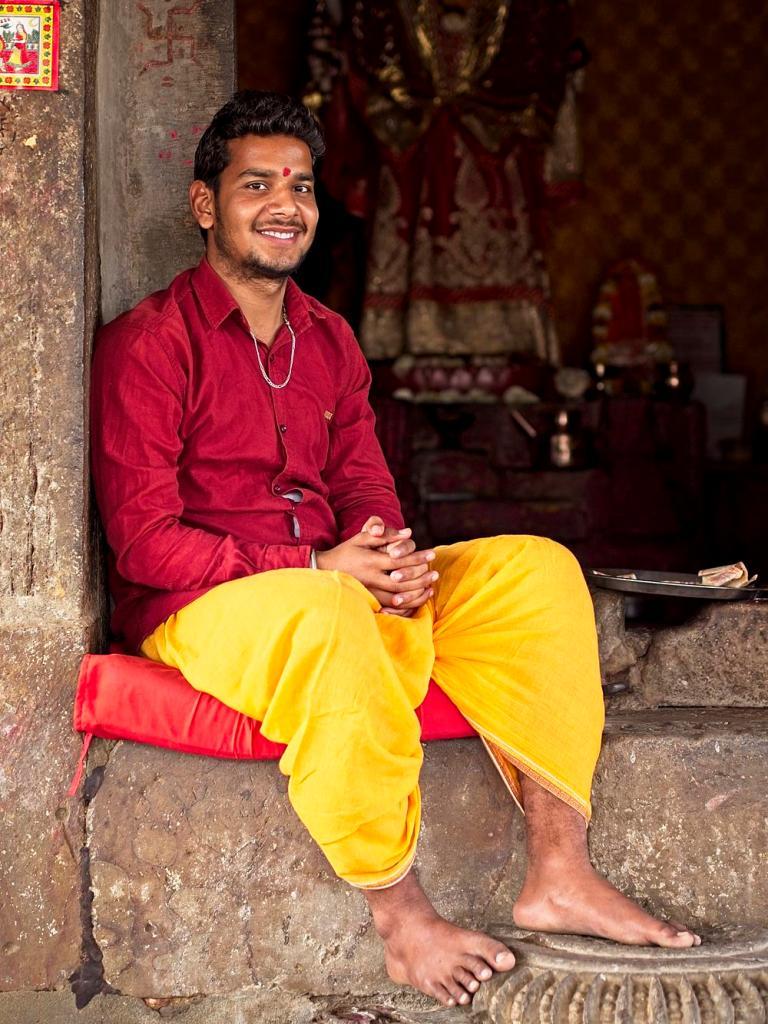 Priest wearing red and yellow at Sankat Mochan Balaji Mandir Temple, India by Sam Davis Professional Travel Portrait Photographer